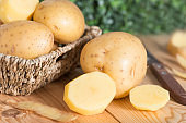 Raw potato food. Fresh potatoes on wooden basket.