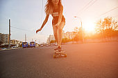 Beautiful young girl with tattoos riding longboard in sunny weather