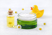 baby care products, natural cream, massage oil and fresh chamomile flowers