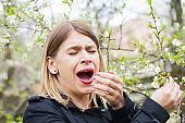 Allergic woman sneezing outdoor on springtime