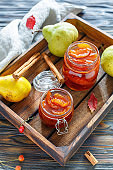 Jam from pears in glass jars and fresh pear.