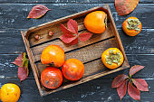 Juicy ripe persimmon in a wooden box.