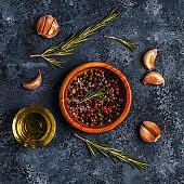 Dark food background with rosemary, garlic and pepper