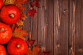 Autumn background with colored leaves and pumpkins on wooden background.