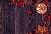 Autumn background with hot chocolate, knitted scarf, multi-colored leaves.