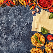 Italian food background with pasta, spices and vegetables.