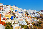 picturesque village and the rest in the traditional white houses in Oia, Santorini, Greece