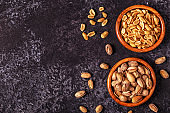 Salted pistachios and peanuts on stone background.