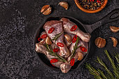 Raw chicken legs with rosemary, garlic and chilli.