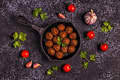 Roasted  meatballs with tomatoes, garlic and parsley.