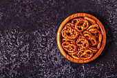 Salted pretzel in a bowl on stone background.
