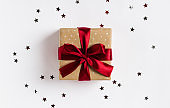Christmas holiday gift box red bow on decorated festive table with sparkle stars