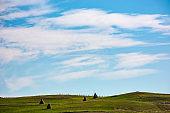 hay stacks on hillside under the beautiful sky