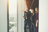 Three business persons near office window