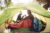 smiling couple of tourists drinking coffee from mugs in the tent