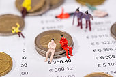small toy people with euro coin and business graph.