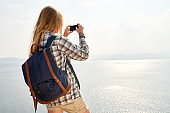 Backpacker photographing ocean