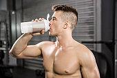Shirtless man on bench drinking protein shake