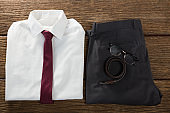 Folded school uniform, belt and spectacle on wooden plank