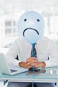 Blue balloon with sad face hiding businessmans face