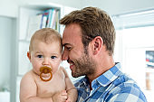 Happy father with cute son at home