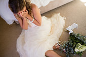 High angle view of bride in wedding dress crying while sitting by bed