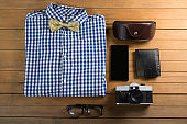 Folded shirt, spectacle, camera, wallet, and mobile phone on wooden plank