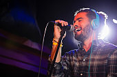 Man listening to headphones while singing on microphone