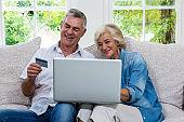 Senior couple shopping online using laptop at living room