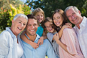 Smiling family and grandparents in the countryside embracing