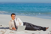 Smiling young businessman lying on the sand with his laptop