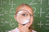 Cute schoolgirl looking through a magnifying glass