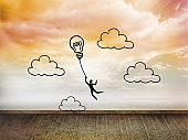 Light bulb balloon on wall with bright sky