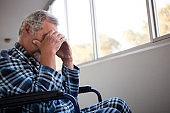 Side view of sad senior man sitting on wheelchair