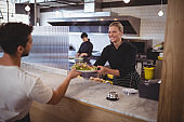 Smiling female chef giving fresh Greek salad to waiter