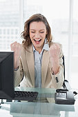Businesswoman cheering with clenched fists in office