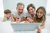 Smiling family using laptop on bed in bedroom