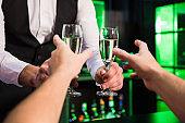 Bartender serving glass of champagne