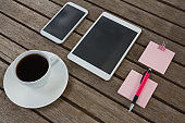 Black coffee, mobile phone, digital tablet, pen and sticky note on wooden plank