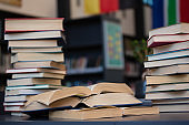 Stack of books on wooden table against shelf
