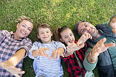 Happy family lying on the grass and making hand gestures
