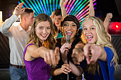 Female friends singing song together in bar