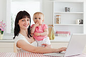 Lovely brunette woman relaxing with her laptop next to her baby while sitting