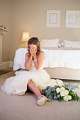 Bride in wedding dress crying while sitting by bed