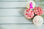 Overhead view of Breast Cancer Awareness pink ribbons on cupcakes