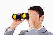 Man in a suit using binoculars