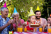 Family celebrating birthday at table in yard