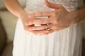 Midsection of bride wearing wedding ring at home