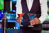 Bartender serving blue and orange cocktail drinks
