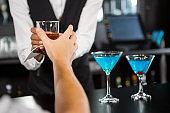 Bartender serving whiskey at bar counter